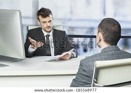 Young executive unsatisfied with the performance of the employee, demanding explanation - concept  - stock photo