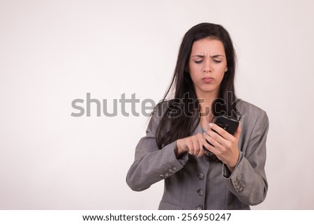 Young executive woman dressed in grey with a cellular texting and seriously face - stock photo