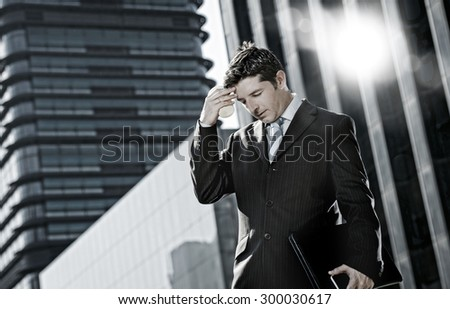 young exhausted businessman standing outdoors on street in front of business buildings at financial district suffering headache and work stress holding take away coffee - stock photo