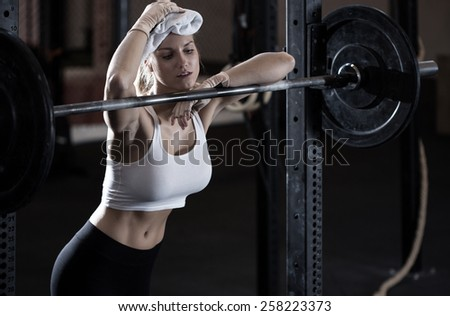 Young exhausted weightlifting girl after training - stock photo