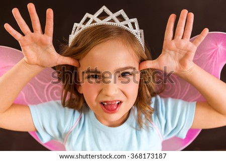 Young fairy with pink wings and white crown on her head shows a funny physiognomy against dark background, close-up - stock photo