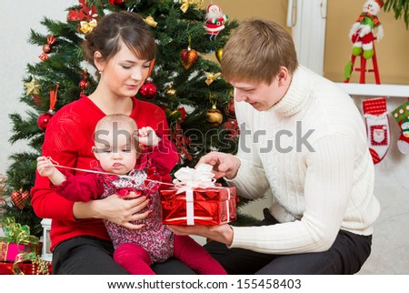 Young family at Christmas tree at home - stock photo