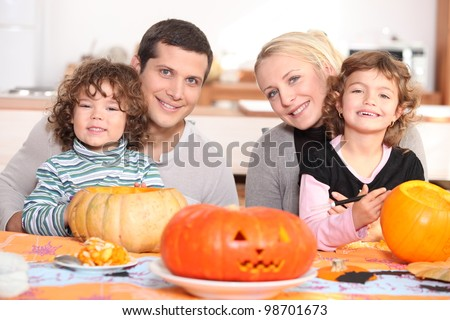 Young family carving pumpkins - stock photo