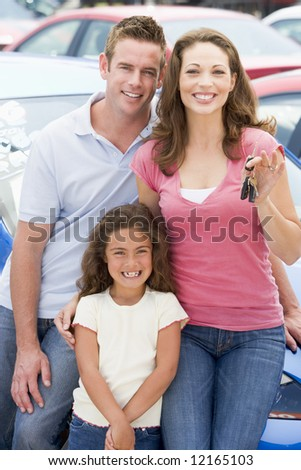 Young family collecting new car from lot - stock photo