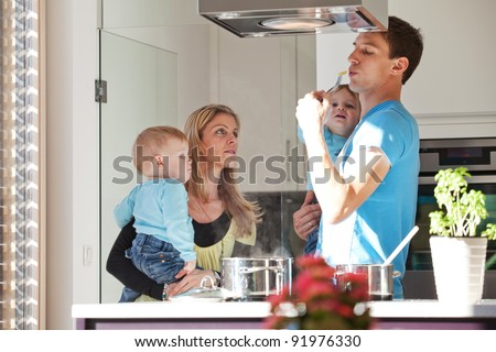 Young family cooking in a modern kitchen setting - stock photo