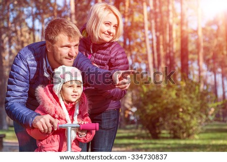 Young Family Father Mother and Little Child in Autumnal Forest Pointing and Looking - stock photo