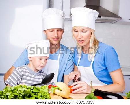 young family; father, mother and their five year old son cook together in the kitchen at home - stock photo