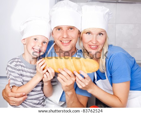 young family; father, mother and their five year old son eating bread together in the kitchen at home - stock photo