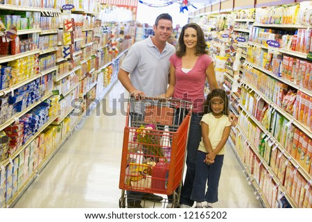 Young family grocery shopping in supermarket - stock photo