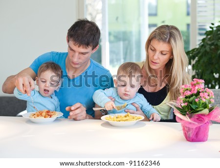 Young family having a hard time feeding baby twins - stock photo
