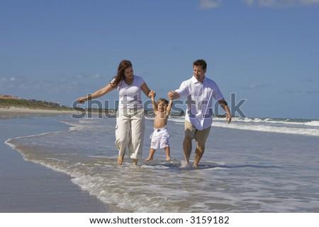 Young family heaving fun on a beach - stock photo