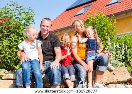 young family in front of home or house with three children sitting in the sun - stock photo