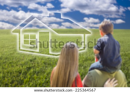Young Family in Grass Field with Ghosted House In Front of Them. - stock photo