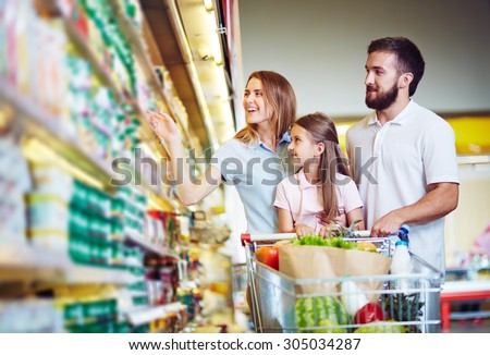 Young family in hypermarket choosing products - stock photo