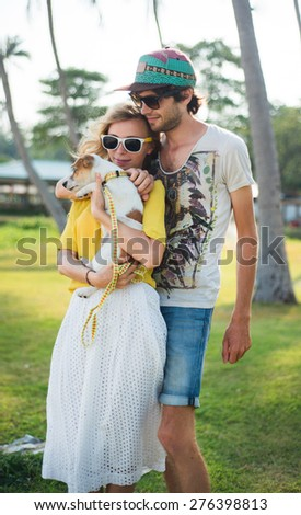 Young family in love on the beach in summer sunny evening with little dog.Summer mood,summer portrait of young couple in love,wearing sunglasses,hipster couple on island,tropical romance,bright color  - stock photo