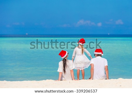 Young family in Santa hats during Christmas vacation - stock photo