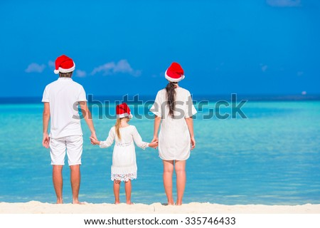 Young family in Santa hats relaxing on tropical beach during Christmas vacation - stock photo
