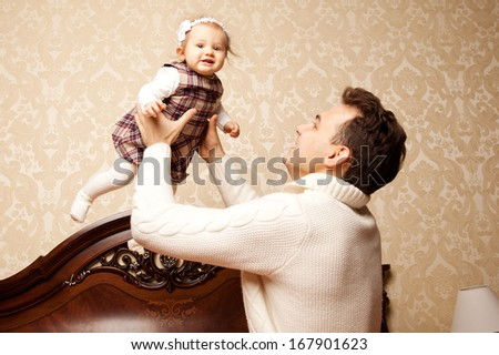 Young family in the bedroom. Father and daughter in the interior. Dad and baby are playing together. - stock photo