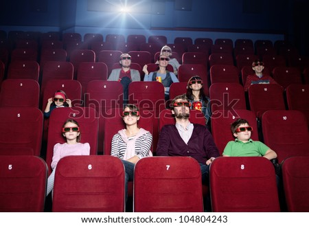 Young family in the 3d movie theater - stock photo