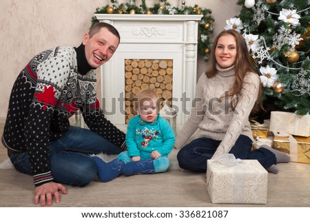 Young family is preparing for Christmas at interior studio - stock photo