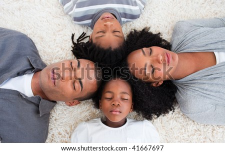 Young family lying on floor with their heads together - stock photo