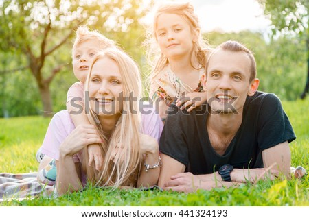 Young family lying on grass in countryside - stock photo