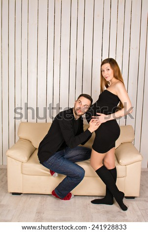 young family. man put his ear to the belly of his pregnant wife and listening unborn baby's heartbeat . lovers on a white sofa. expectant parents - stock photo