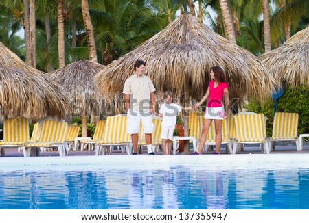 Young family next to a beautiful swimming pool at a tropical res - stock photo