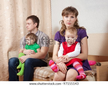 young family of four after quarrel in home - stock photo