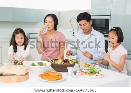 Young family of four enjoying healthy meal in the kitchen at home - stock photo