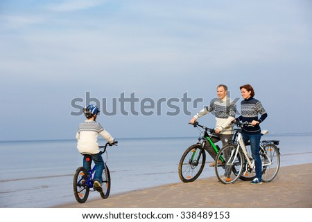 Young family of three riding bicycles on sand beach - stock photo