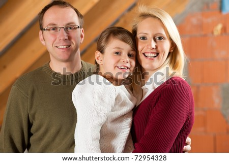 Young family on a construction site; it is their new home - stock photo