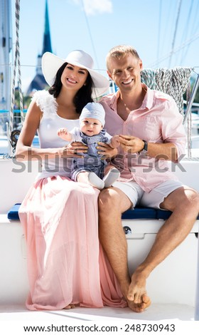 Young family on a sailing boat. Mother, father and a baby. - stock photo