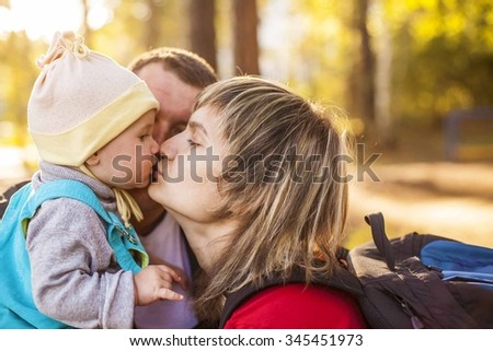 young family on the walk. Little daughter sits on mother's hand and kissing mom. Dad between wife and daughter. Nice lovely kid outdoor in autumn park against sunset forest trees - stock photo