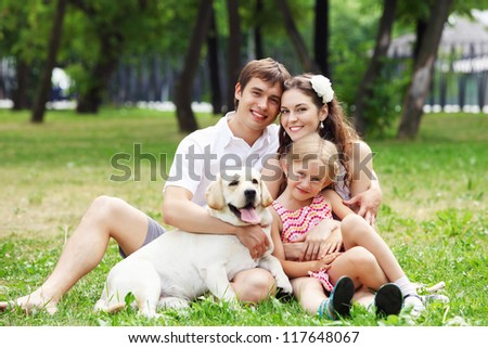 Young Family Outdoors in summer park with a dog - stock photo