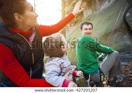Young family outdoors is climbing on the rocks during the holidays. - stock photo