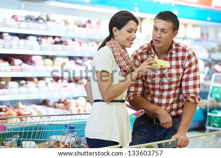 Young Family people choosing bio food cheese in grocery supermarket during weekly shopping - stock photo