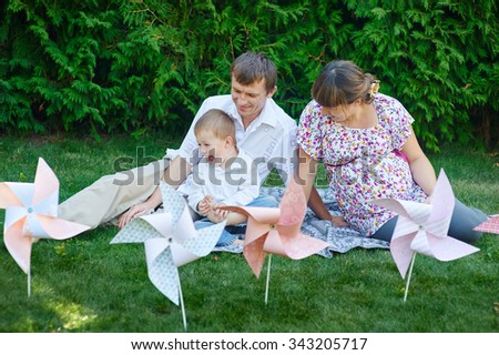 young family playing on a picnic in the summer park. - stock photo