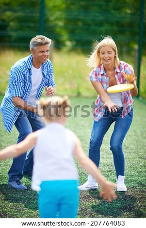 Young family playing with flying disc in the countryside - stock photo