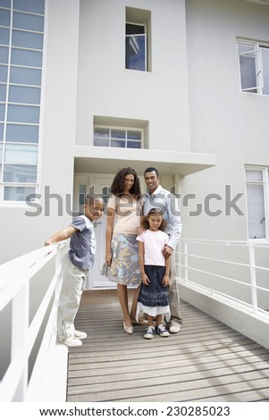Young Family Posing outside House and Smiling - stock photo