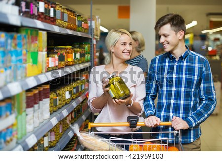 Young family purchasing canned food for week at supermarket - stock photo