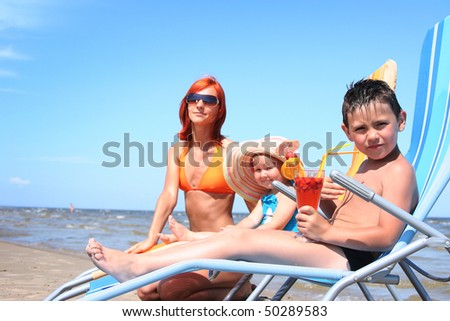 young family relaxing on beach (boy in focus) - stock photo
