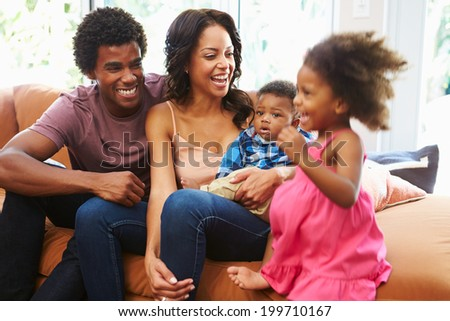 Young Family Relaxing On Sofa Together - stock photo