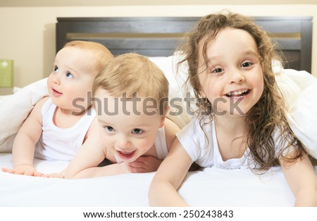 Young family resting together in parent's bed - stock photo