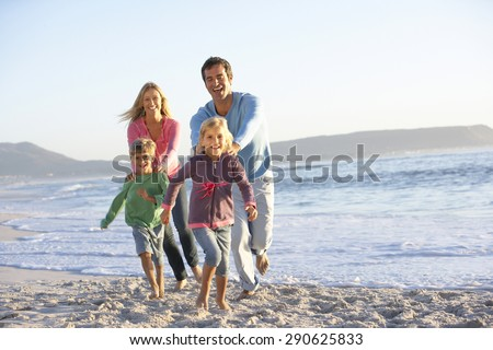 Young Family Running Along Sandy Beach On Holiday - stock photo