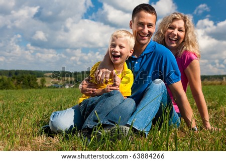 Young family sitting in the sun on the meadow an a bright summer day - stock photo
