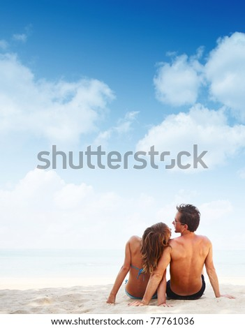 Young family sitting on warm sand by a sea with blue sky background - stock photo