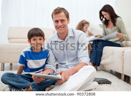 Young family spending free time in the living room - stock photo