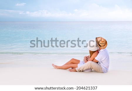 Young family spending summer vacation on romantic beach resort, sitting and enjoying seascape, romance and affection concept - stock photo