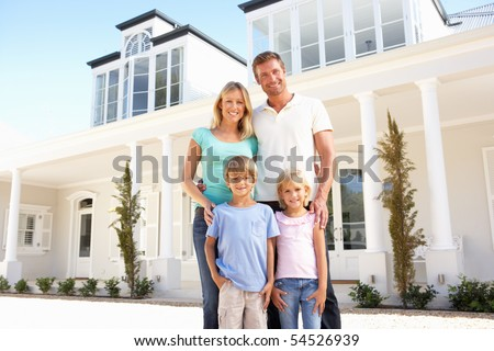 Young Family Standing Outside Dream Home - stock photo